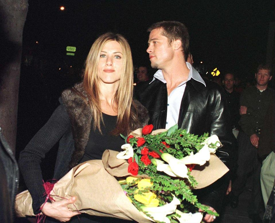 """<p>Pitt and Jennifer Aniston <a href=""""https://www.eonline.com/news/1013930/the-truth-about-brad-pitt-and-jennifer-aniston-s-current-relationship"""" rel=""""nofollow noopener"""" target=""""_blank"""" data-ylk=""""slk:reportedly"""" class=""""link rapid-noclick-resp"""">reportedly</a> met after Pitt had their agents set them up on a date in 1998. Here they are leaving Los Angeles' Barfly nightclub, where he threw her a massive 30th birthday party in February 1999.</p>"""