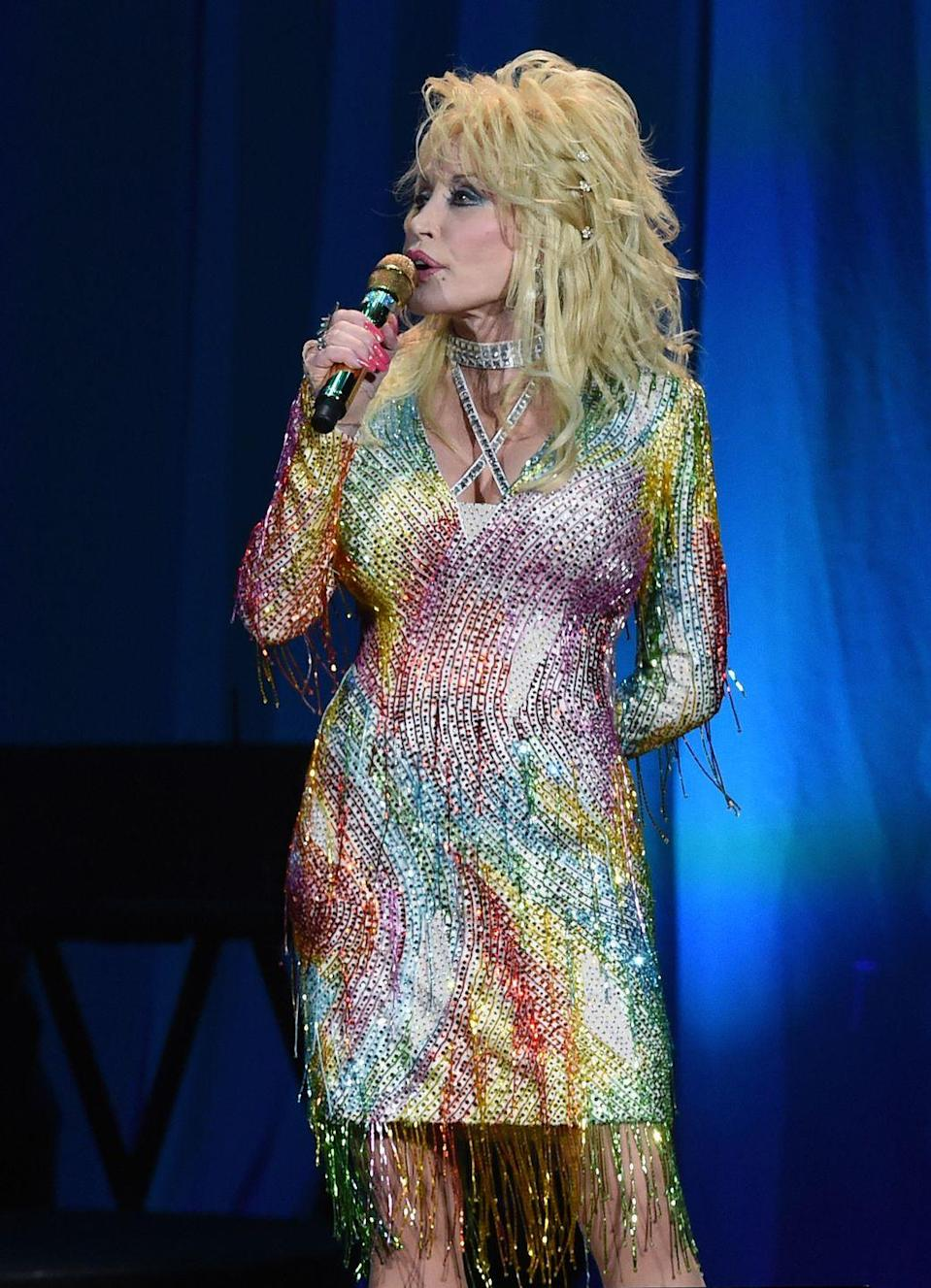 """<p>Here, Parton's dress pays homage to one of her most beloved songs, """"Coat of Many Colors,"""" inspired by her own childhood experience. This beaded rainbow overlay with rhinestones is Dolly at her finest. </p>"""