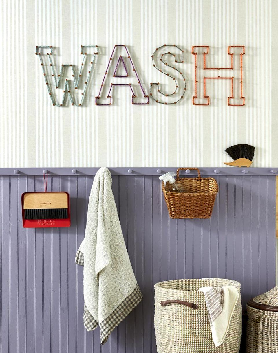 """<p>Update a laundry room wall with a craft straight from the 70s: string art. Want to give it a go in other rooms, too? Try writing """"PLAY"""" in a kids room or """"REST"""" in a bedroom.<strong><br><br>To make: </strong>Start by cutting out letters from craft paper. Mark nail holes with a pencil on the wall using the letters as a guide. Hammer copper nails into the wall, and wrap nails with lengths of assorted-colored thick yarn.<br></p>"""