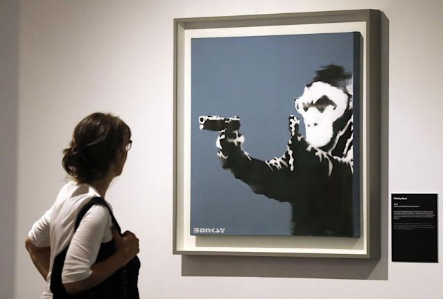 <p>A visitor looks at the painting 'Monkey Guns' by British Banksy during the exhibition 'The Art of Banksy' in Berlin, Germany on June 20, 2017. (Felipe Trueba/EPA/REX/Shutterstock) </p>