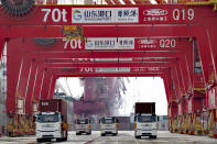 Container trucks pass through a new automated container port in Rizhao in eastern China's Shandong province on Oct. 9, 2021. China's import and export growth slowed in September amid shipping bottlenecks and other disruptions combined with coronavirus outbreaks. (Chinatopix via AP)