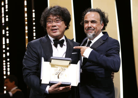 """72nd Cannes Film Festival - Closing ceremony - Cannes, France, May 25, 2019. Director Bong Joon-ho, Palme d'Or award winner for his film """"Parasite"""" (Gisaengchung), reacts next to Alejandro Gonzalez Inarritu, Jury President of the 72nd Cannes Film Festival. REUTERS/Stephane Mahe"""