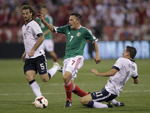 Mexico's Christian Gimenez, center, is tripped by the United States' Alejandro Bedoya, right, as Kyle Beckerman helps to defend during the first half of a World Cup qualifying soccer match Tuesday, Sept. 10, 2013, in Columbus, Ohio. (AP Photo/Jay LaPrete)