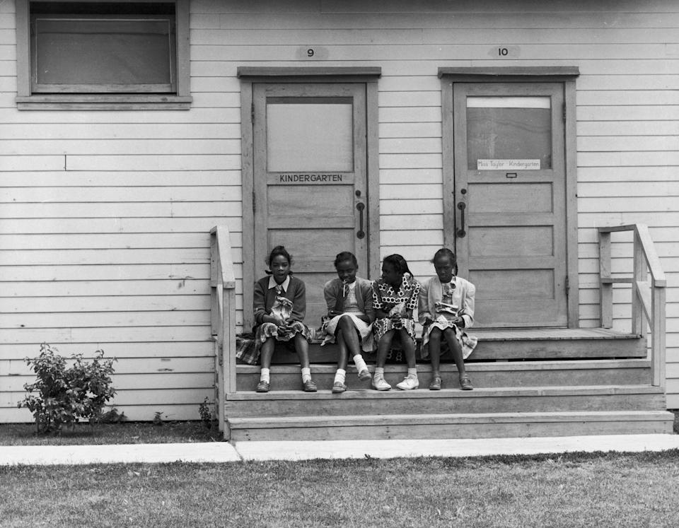 <p>Four young students wait on the steps of their schoolhouse in 1945, a time when schools were still segregated in America.</p>
