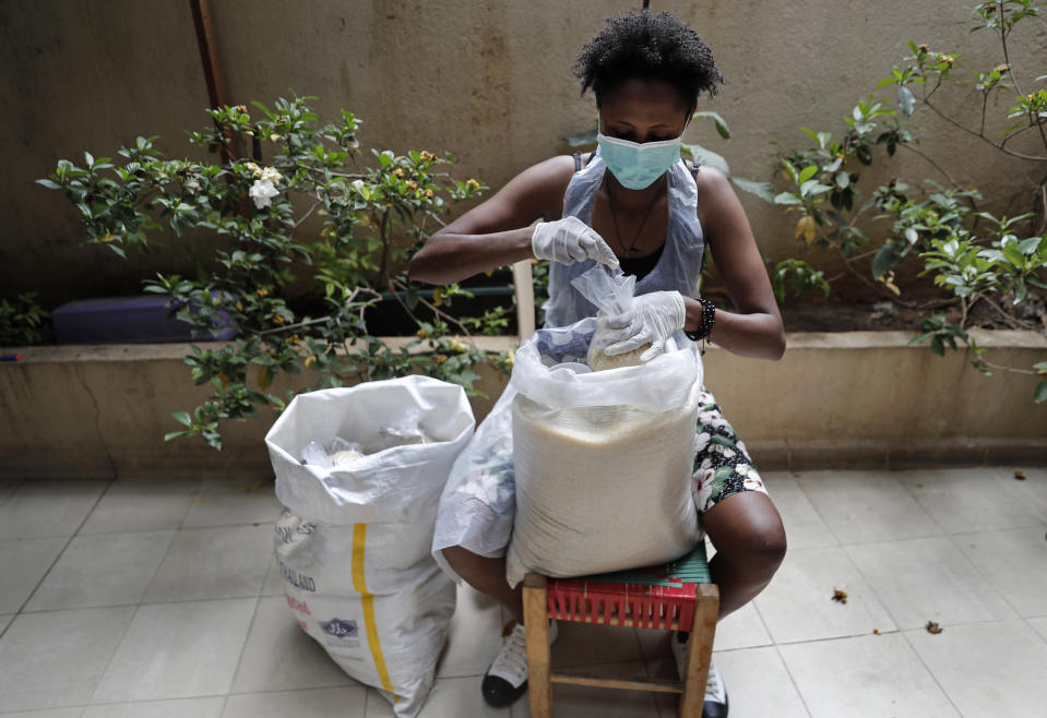 """In this Saturday, May 23, 2020 photo, an Ethiopian worker packs food at the office of Egna Legna, meaning """"from us migrants to us migrants"""" in Amharic, Ethiopia's official language, which offers food packages for some who lost their jobs and helps others pay rent, in Beirut, Lebanon. Some 250,000 registered migrant laborers in Lebanon — maids, garbage collectors, farm hands and construction workers — are growing more desperate as a crippling economic and financial crisis sets in, coupled with coronavirus restrictions. With no functioning airports and exorbitant costs of repatriation flights, many are trapped, unable to go home. (AP Photo/Hussein Malla)"""