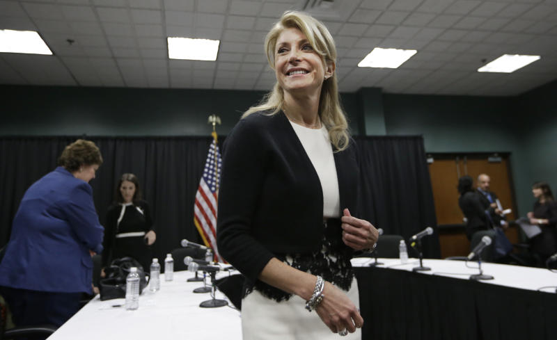 FILE - In this Jan. 9, 2014 file photo, Texas Sen. Wendy Davis smiles as she heads to speak to reporters after an education roundtable meeting in Arlington, Texas. Davis is expected to face Republican Greg Abbott in the Texas governor's race. Battleground Texas, a major Democratic effort aimed at turning one of the reddest states blue, will face its first test in the Democratic primary on March 4. (AP Photo/LM Otero)