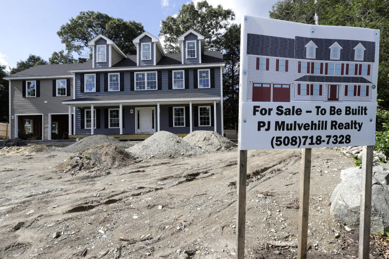 In this Sept. 3, 2019 photo a for sale sign, right, rests in front of a newly constructed home, in Norwood, Mass. On Thursday, Oct. 17, the Commerce Department reports on U.S. home construction in September. (AP Photo/Steven Senne)