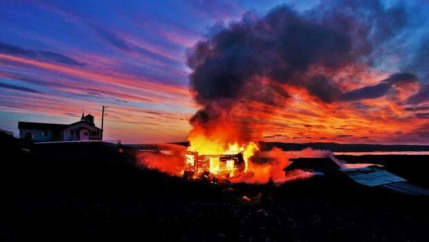 A home in Tsiigehtchic, N.W.T. was completely destroyed by flames early Saturday morning, according to community's fire chief, Albert Ross.  (Submitted by Lawrence Norbert - image credit)