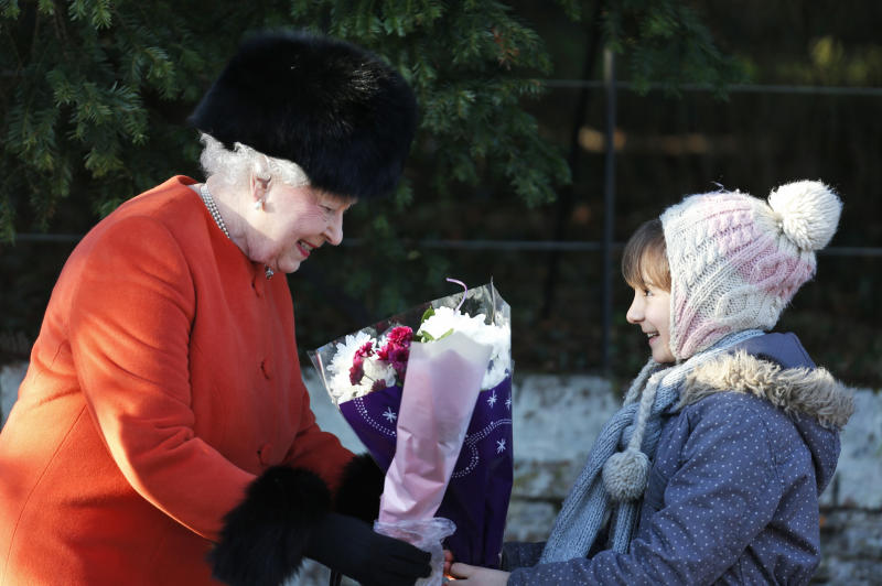 Britain's Queen Elizabeth II receives flowers from a young girl after she and other members of the royal family attended a Christmas Day Service at St. Mary's church on the grounds of Sandringham Estate, the Queen's royal estate in Norfolk, England, Wednesday, Dec. 25, 2013. (AP Photo/Lefteris Pitarakis)