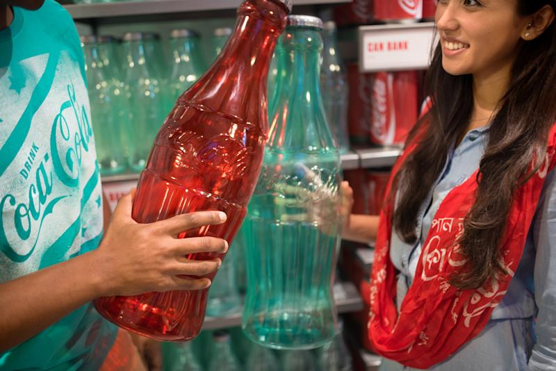 Two shoppers hold Coca-Cola bottle banks at the Coca-Cola store.