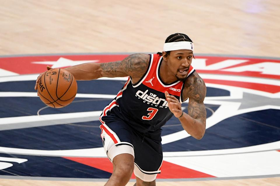 Bradley Beal dribbles with one hand as he leans into a drive.