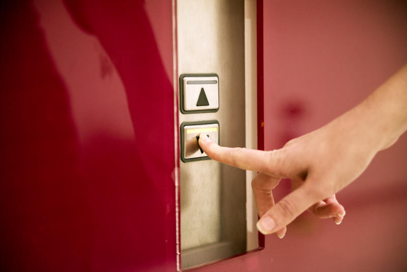 Business women pressing elevator button. finger presses the elevator button. lift. high floor.hand reaches for the button of the elevator call.touching going up sign lift control panel