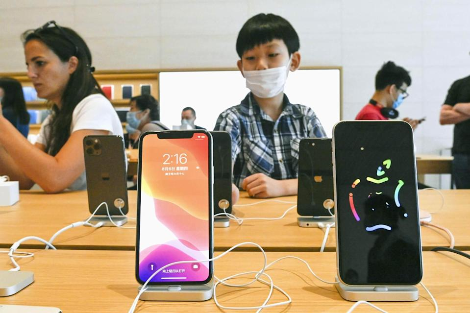 Visitors look at iPhones at an Apple store in Beijing, China, on August 6, 2020. Photo: Kyodo