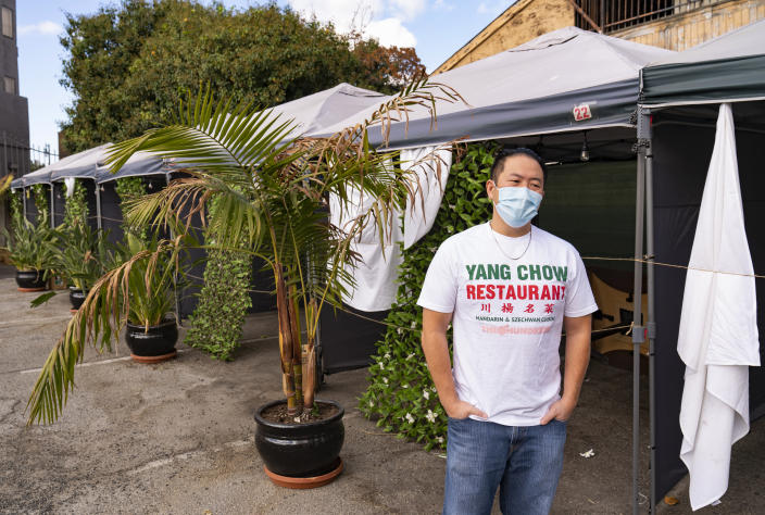 Benny Yun, owner of Yang Chow restaurant pauses next to now unused plastic tents set for clients to be able to eat outdoors on the parking lot of his business in Los Angeles, Thursday, Dec. 17, 2020. Bigotry toward Asian Americans and Asian food has spread steadily alongside the coronavirus in the United States. Yun said even though his businesses have survived the pandemic, they get prank calls almost daily asking if they have dog or cat on the menu or impersonating a thick Asian accent. (AP Photo/Damian Dovarganes)