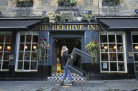 A worker removes tables from outside the Beehive Inn, as temporary restrictions announced by First Minister Nicola Sturgeon to help curb the spread of coronavirus have come into effect from 6pm, in Edinburgh, Friday, Oct. 9, 2020. (Andrew Milligan/PA via AP)