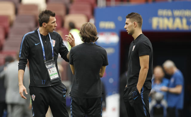 Croatia's Mario Mandzukic, left gestures as he speaks to Croatia's Luka Modric, centre, and Croatia's Marko Pjaca as they walk around the stadium pitch before the start of the final match between France and Croatia at the 2018 soccer World Cup in the Luzhniki Stadium in Moscow, Russia, Sunday, July 15, 2018. (AP Photo/Francisco Seco)