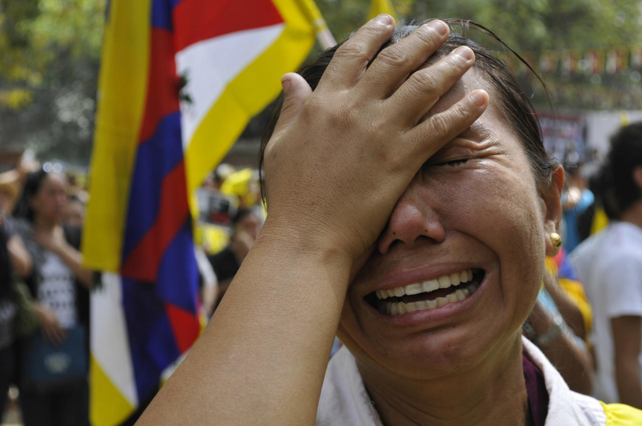 An exile Tibetan woman cries after Jampa Yeshi, a Tibetan self immolated during a protest, in New Delhi, India, Monday, March 26, 2012, just ahead of a visit by China's president Hu Jintao and following self-immolations in the Himalayan region against Beijing's rule.(AP Photo/Tsering Topgyal)