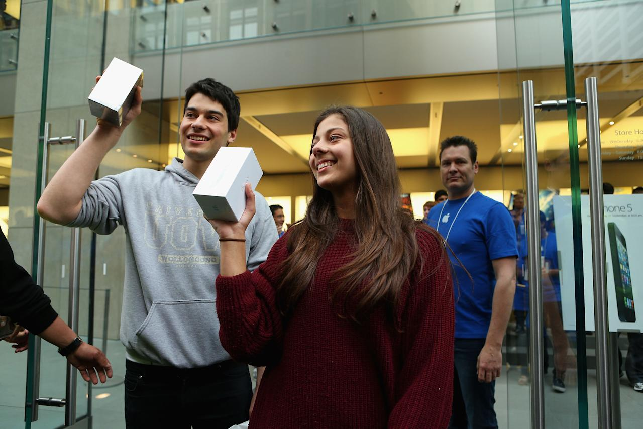 SYDNEY, AUSTRALIA - SEPTEMBER 21: The first  customers to purchase their new iPhone 5 phone's exit the Apple flagship store on George street on September 21, 2012 in Sydney, Australia. Australian Apple stores are the first in the world to receive and sell the new iPhone 5 handsets.  (Photo by Cameron Spencer/Getty Images)