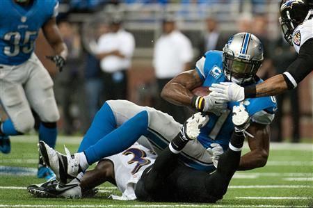 Detroit Lions wide receiver Calvin Johnson (81) is tackled by Baltimore Ravens strong safety James Ihedigbo (32) and cornerback Jimmy Smith (22) during the fourth quarter at Ford Field. Tim Fuller-USA TODAY Sports