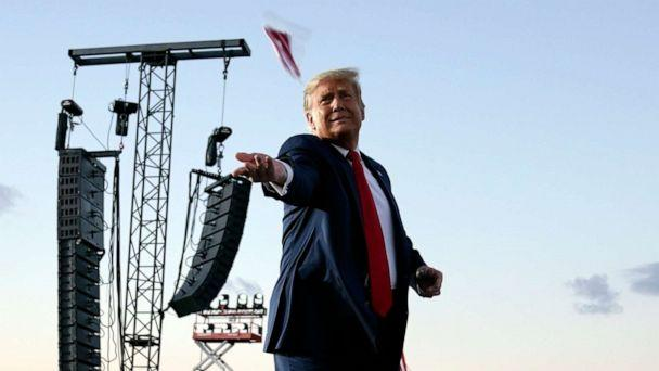PHOTO: President Donald Trump throws face masks into the crowd as he arrives for a campaign rally at Orlando Sanford International Airport, Oct. 12, 2020, in Sanford, Fla. (Evan Vucci/AP)