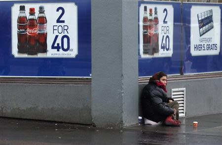 File photo shows a woman begging for money outside a shop in downtown Bergen, southwestern Norway