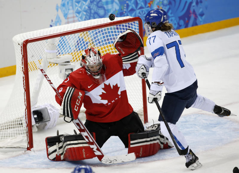 Goalkeeper Shannon Szabados of Canada blocks a shot at the goal under pressure from Susanna Tapani of Finland during the third period of the 2014 Winter Olympics women's ice hockey game at Shayba Arena, Monday, Feb. 10, 2014, in Sochi, Russia. Canada defeated Finland 3-0. (AP Photo/Petr David Josek)