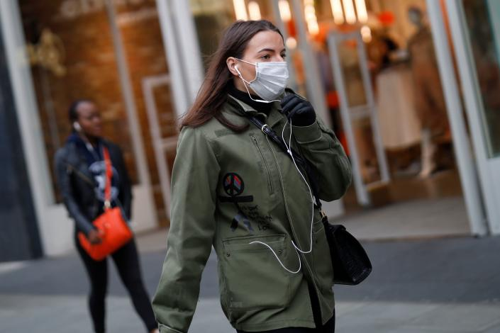 A woman is pictured wearing a mask while walking down Oxford Street, central London, on 17 March. The UK has confirmed 1,960 cases since the outbreak began. (Getty Images)