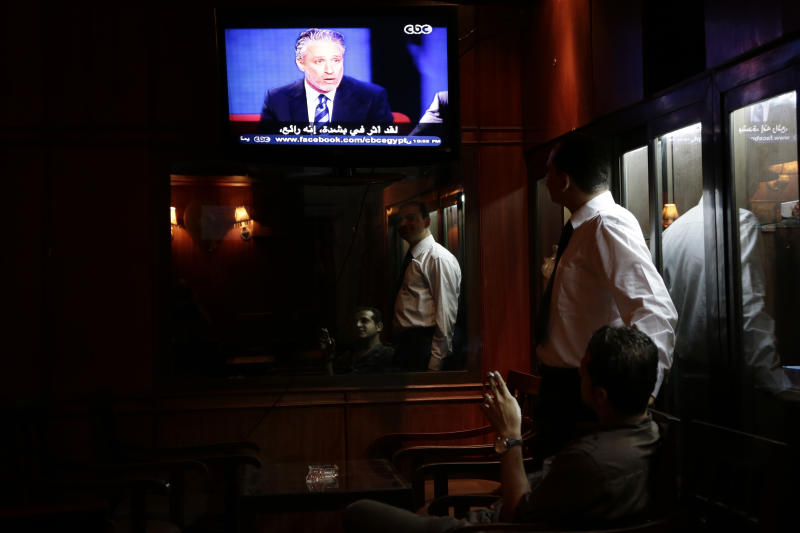 "Egyptian men reflected on mirror as they watch Jon Stewart on a TV screen at a coffee shop, in Cairo, Egypt, Saturday, June 22, 2013. Jon Stewart has appeared on Egypt's top satirical TV program, modeled after his own program ""The Daily Show."" Stewart was brought to the set wearing a black hood and introduced by host Bassem Youssef as a captured foreign spy. (AP Photo/Hassan Ammar)"