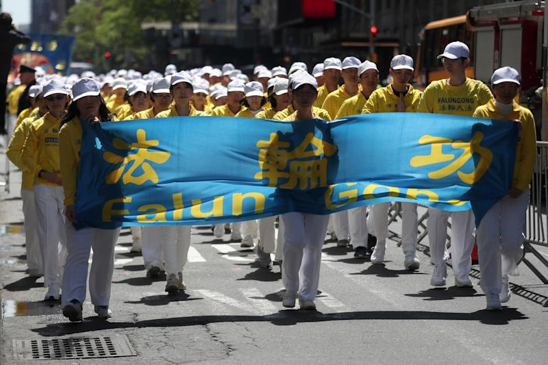Members of Falun Gong or Falun Dafa, a Chinese religious spiritual practice, march to the Consulate General of the People's Republic of China in New York City