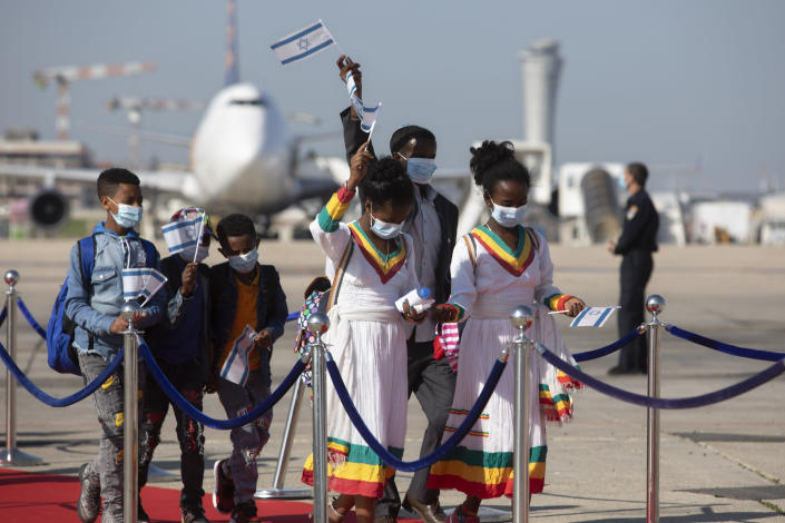 Ethiopian immigrants arrive at the Ben Gurion airport near Tel Aviv, Israel, Thursday, Dec. 3, 2020. Hundreds of Ethiopian immigrants on Thursday arrived to a festive ceremony at Israel's international airport, as the government took a step toward carrying out its pledge to reunite hundreds of families split between the two countries. (AP Photo/Sebastian Scheiner)