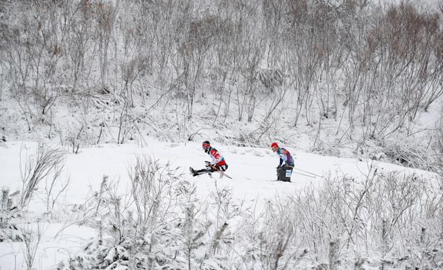 Biathlon - Pyeongchang 2018 Winter Paralympics - Men's 15km - Sitting - Alpensia Biathlon Centre - Pyeongchang, South Korea - March 16, 2018 - Collin Cameron of Canada and Daniel Cnossen of the U.S. (30) compete. REUTERS/Carl Recine