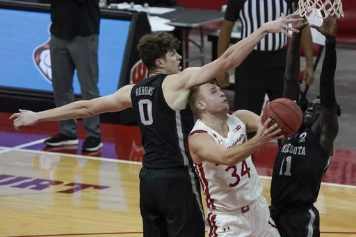 Wisconsin's Brad Davison shoots between Minnesota's Liam Robbins and Both Gach during the second half of an NCAA college basketball game Thursday, Dec. 31, 2020, in Madison, Wis. (AP Photo/Morry Gash)