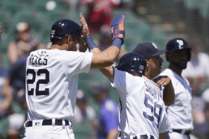 Detroit Tigers' Victor Reyes (22) high fives teammate Zack Short after they both scored on Willi Castro's double during the third inning of a baseball game against the New York Yankees, Sunday, May 30, 2021, in Detroit. (AP Photo/Carlos Osorio)