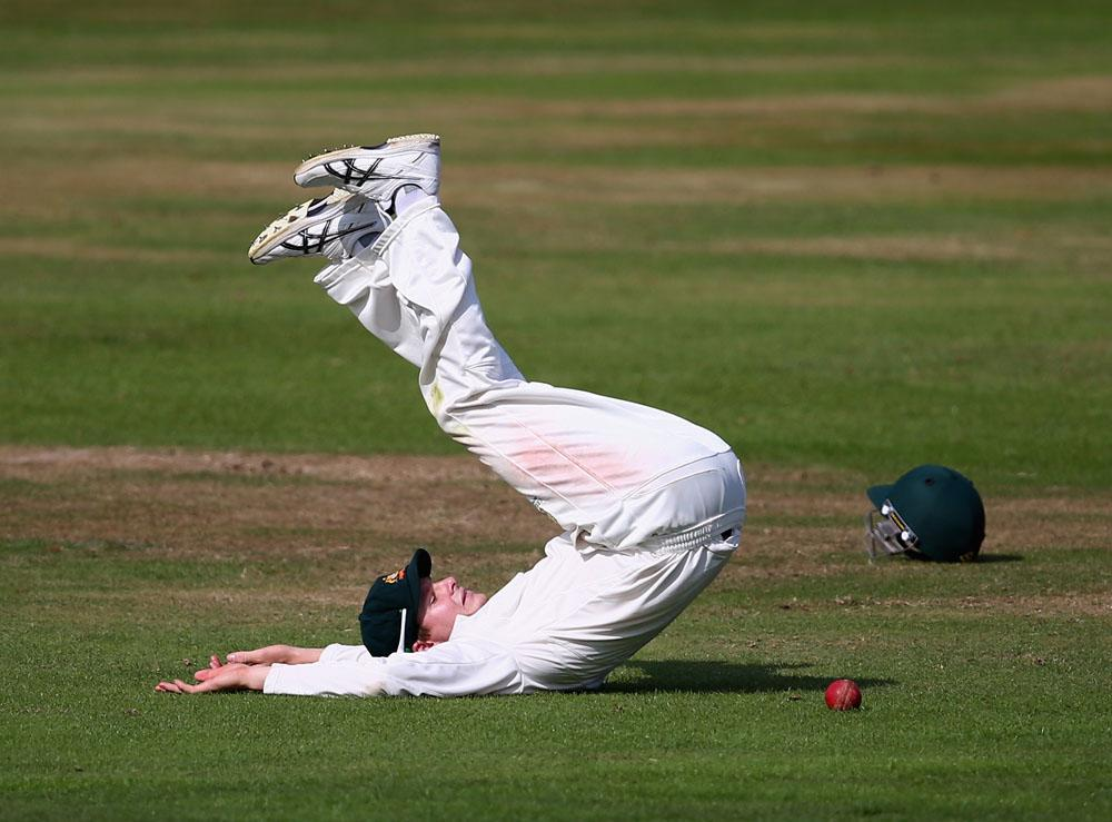 NORTHAMPTON, ENGLAND - AUGUST 16:  Steve Smith of Australia fumbles the ball during Day One of the Tour Match between England Lions and Australia at The County Ground on August 16, 2013 in Northampton, England.  (Photo by Ryan Pierse/Getty Images)