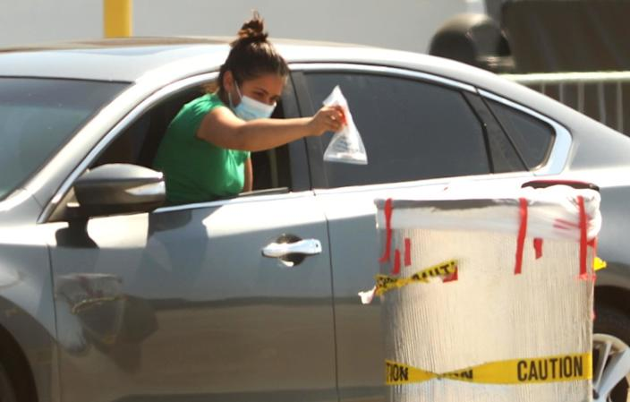 INGLEWOOD, CA - JULY 20, 2020 - - A woman deposits her coronavirus test in a bin at the COVID-19 testing site at The Forum parking lot in Inglewood on Monday, July 20, 2020. (Genaro Molina / Los Angeles Times)