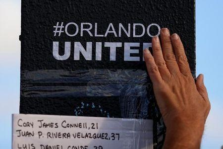 """A person rubs an """"#Orlando United"""" sticker on the sign pole outside Pulse nightclub following the mass shooting last week in Orlando, Florida, U.S., June 21, 2016. REUTERS/Carlo Allegri"""