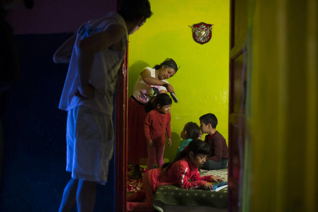 <p>Gabriela Ovid and her husband, Jorge, both from Romania, get their children ready for school as they wait for the police to arrive to evict them in Madrid, June 10, 2014. (AP Photo/Andres Kudacki) </p>