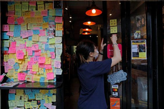 Employee removes stickers and posters with messages in support of the pro-democracy movement at a restaurant in Hong Kong (AP)