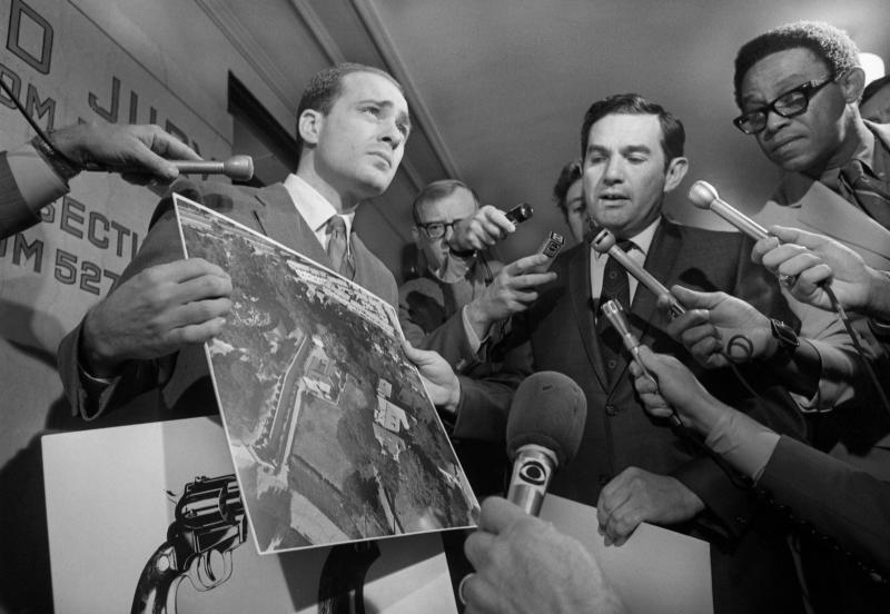 Deputy District Attorneys Aaron Stovitz (left) and Vince Bugliosi display an aerial photograph of the home of Leno and Rosemary LaBianca, victims of a murder last August in which a nomadic hippie group is suspect. They paused for the press as they arrived to testify before a county Grand Jury hearing testimony on the LaBiancas' murder and that of actress Sharon Tate and four others in Miss Tate's Los Angeles mansion.