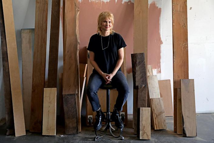 A woman in a black T-shirt and jeans sits amid a bunch of wooden slats.