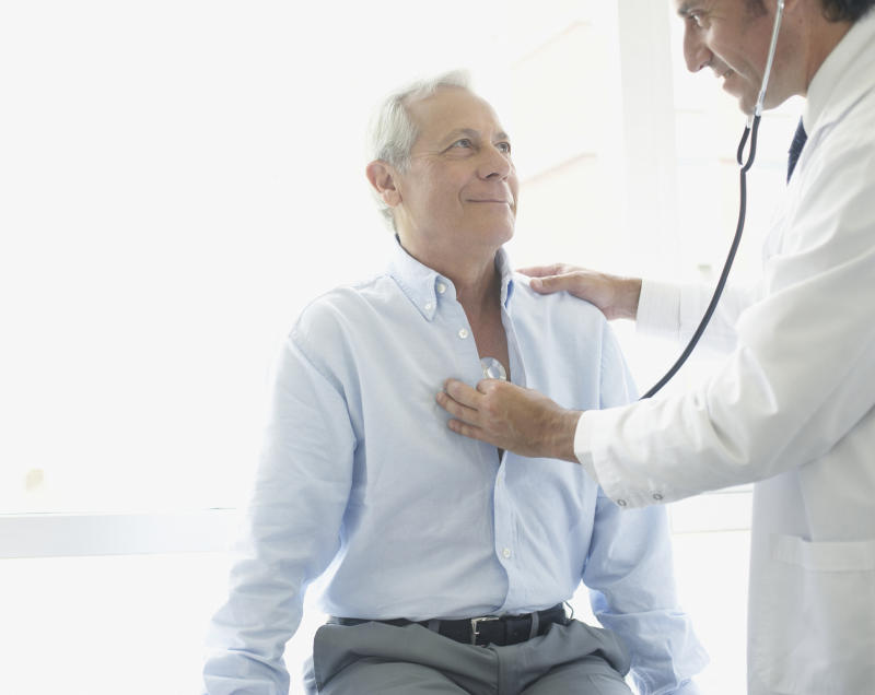 A doctor holds a stethoscope over the chest of an older male patient.