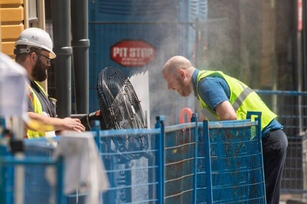 A construction worker uses a misting fan to cool down at a work site in Vancouver, British Columbia on Monday, June 28, 2021.  (Ben Nelms/CBC - image credit)