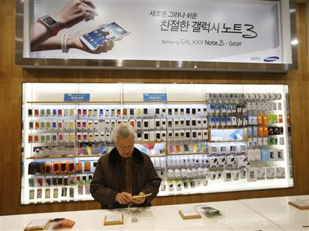 A man tries out a Samsung Electronics' Galaxy S4 at the company's headquarters in Seoul January 6, 2014. REUTERS/Kim Hong-Ji