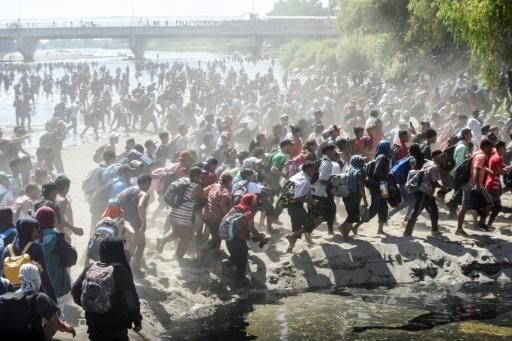Central American migrants - mostly Hondurans travelling in caravan to the US - cross the Suchiate River, the natural border between Guatemala and Mexico, on January 20