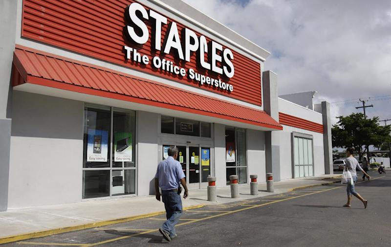 FILE - This March 6, 2013 file photo shows a Staples office supply store Miami. The opening of Postal Service retail centers in dozens of Staples stores around the country is being met with threats of protests and boycotts by the agency's unions. The new outlets are staffed by Staples employees, not postal workers, and labor officials say that move replaces good-paying union jobs with low-wage, nonunion workers. (AP Photo/ Lynne Sladky, File)