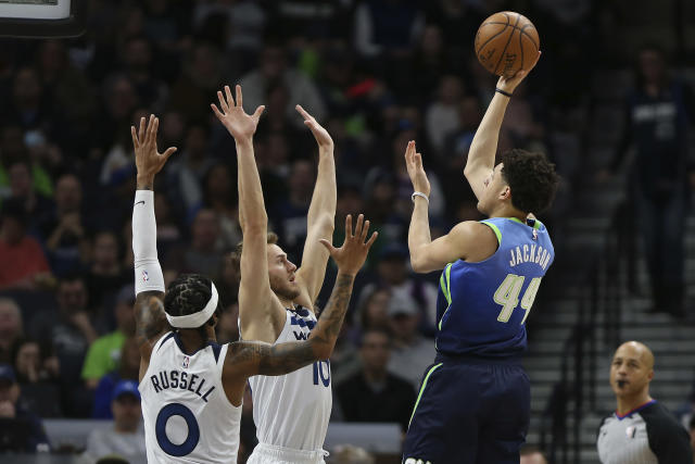 Dallas Mavericks' Justin Johnson lines up a shot against Minnesota Timberwolves' D'Angelo Russell and Jake Layman in the first half of an NBA basketball game Sunday, March 1, 2020, in Minneapolis. (AP Photo/Stacy Bengs)