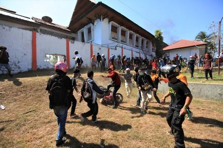 Protesters are seen outside the local parliament building during a protest in Kendari