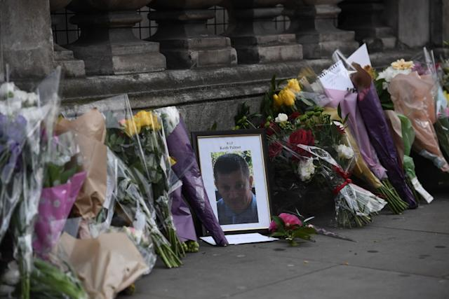 Flowers are left with a memorial to Police Constable Keith Palmer who was stabbed as he tried to stop an attacker in a courtyard outside the Houses of Parliament