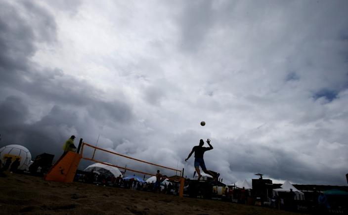 A beach volleyball player leaps to make a serve under stormy skies during the AVP Huntington Beach Open on Friday.