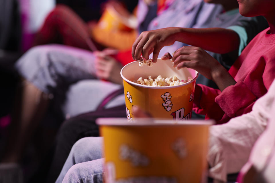 Midsection of friends sharing popcorn in theatre.
